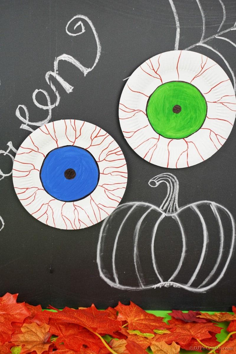 Pappteller blutunterlaufene Augäpfel auf Halloween-Tafel