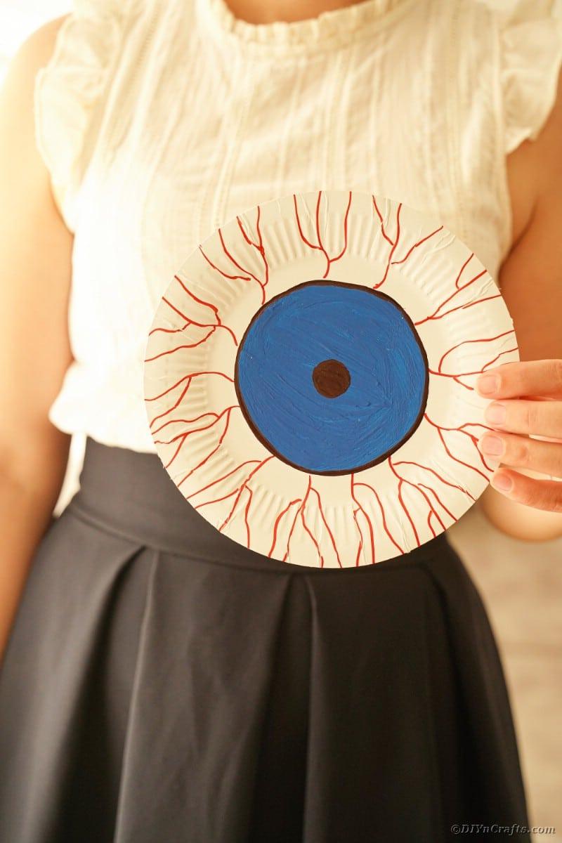Woan holding blue bloodshot eye