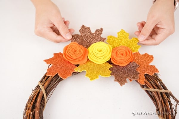 Adding leaves onto grapevine wreath