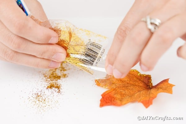 Adding glitter to fall leaf