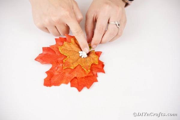 Adding flower to fall leaf boutonniere