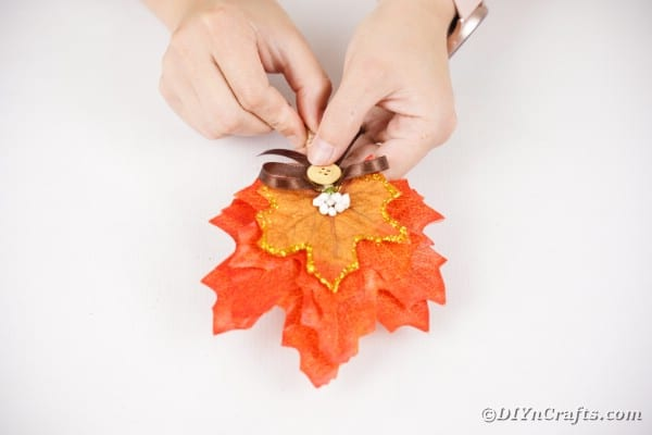 Adding bow to fall leaf boutonniere