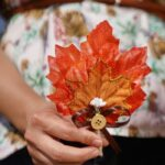 Woman holding fall leaf boutonniere