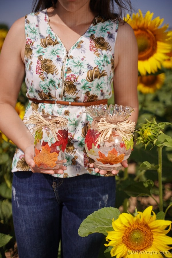 Woman holding upcycled jars with fall leaves