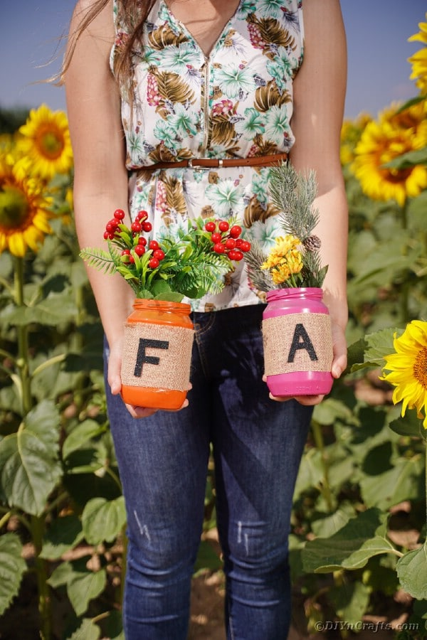 Woman holding fall letter jars