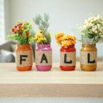 Lettered fall mason jar decor on a table