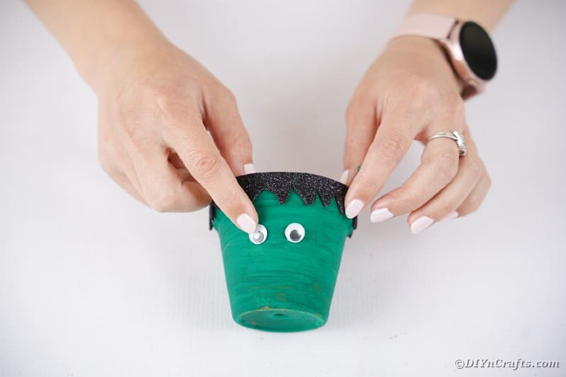 Adding googly eyes to Frankenstein flower pot
