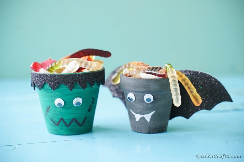 Flower pot Halloween characters on blue table