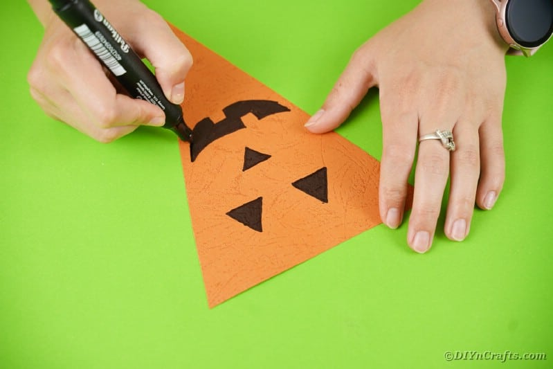 Pumpkin face on triangle