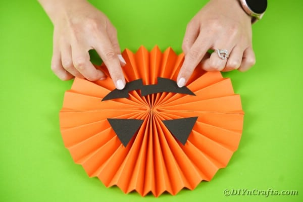Gluing mouth onto pumpkin paper fan