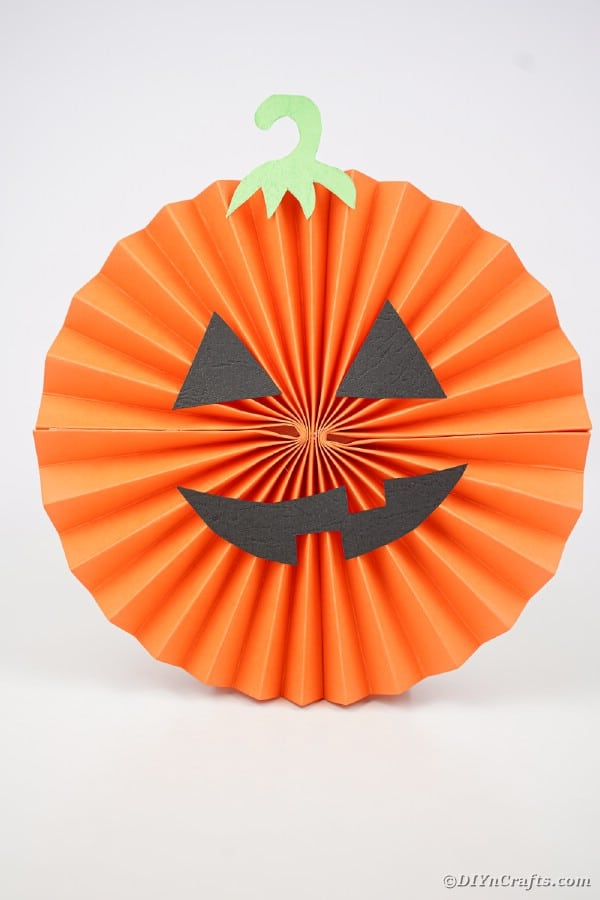 Pumpkin paper fan on white surface