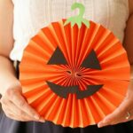 Woman holding paper fan pumpkin