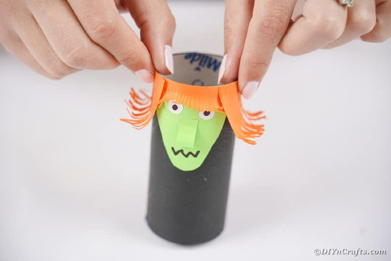 Gluing hair onto witch