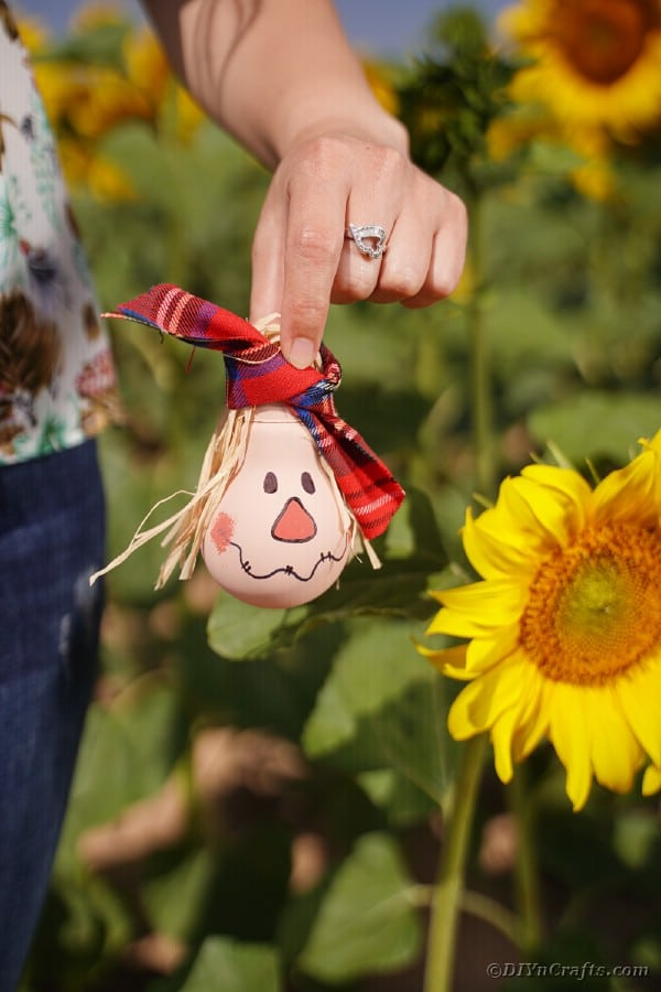 Woman holding a lightbulb scarecrow