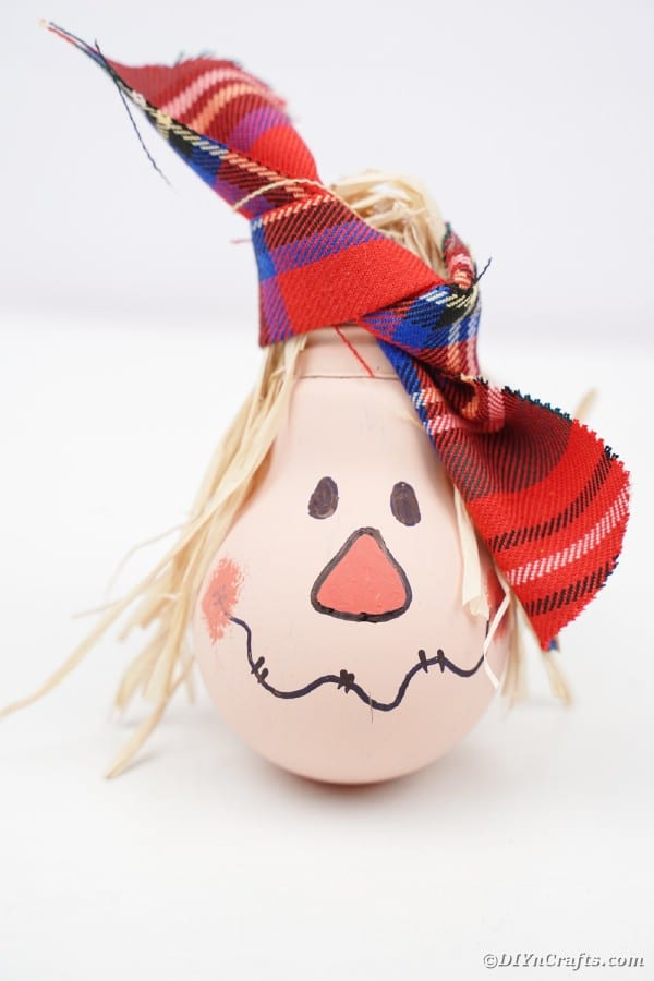 Lightbulb scarecrow on white surface