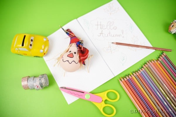 Scarecrow ornament on notebook by pencils