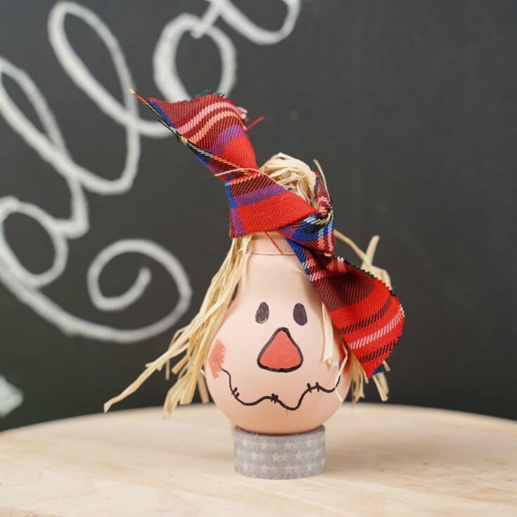 Lightbulb scarecrow on table by chalkboard