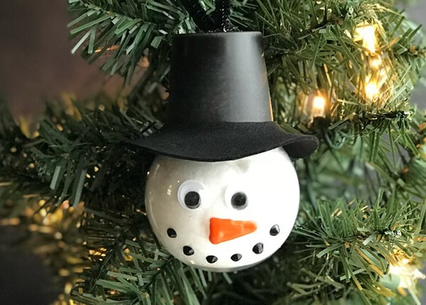 Snowman bulb with hat in tree