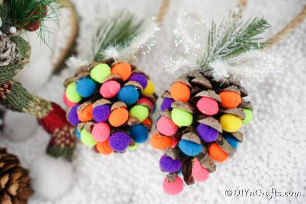 Colored pom poms on pine cones