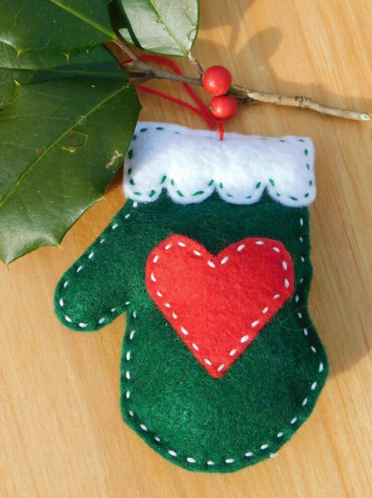 Green felt mitten ornament on wood