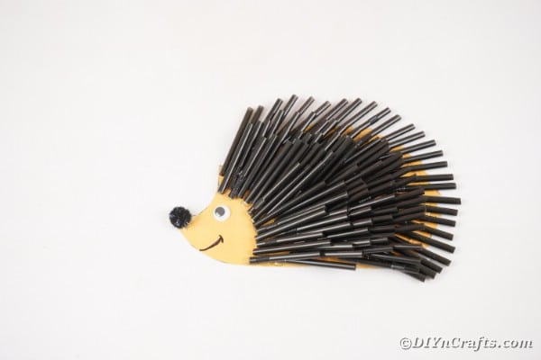 Black straw hedgehog craft on white table