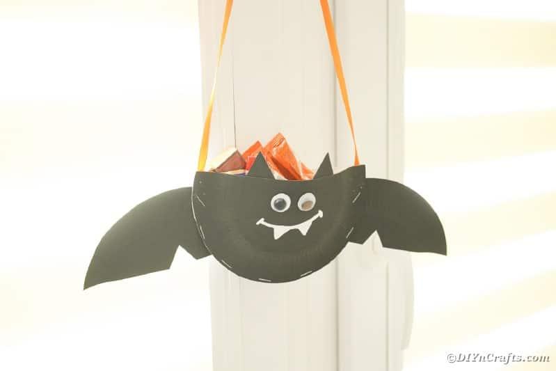 Paper bat hanging on doorknob