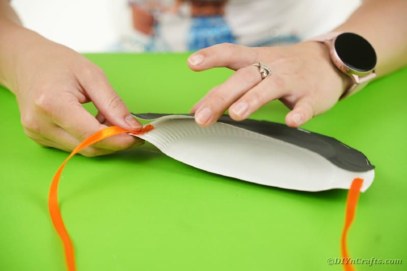 Attaching ribbon to paper plate bat
