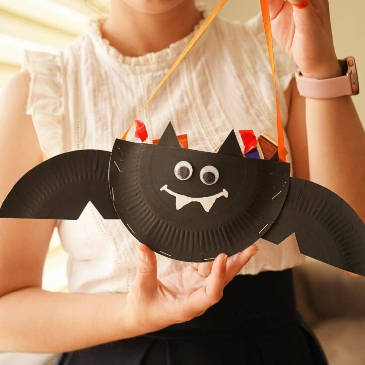 Woman holding a paper plate bat filled with candy