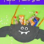 Paper plate bat on gree surface filled with candy