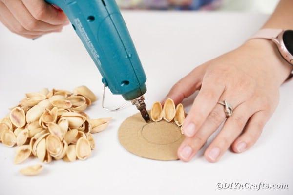 Gluing pistachio shells to cardboard