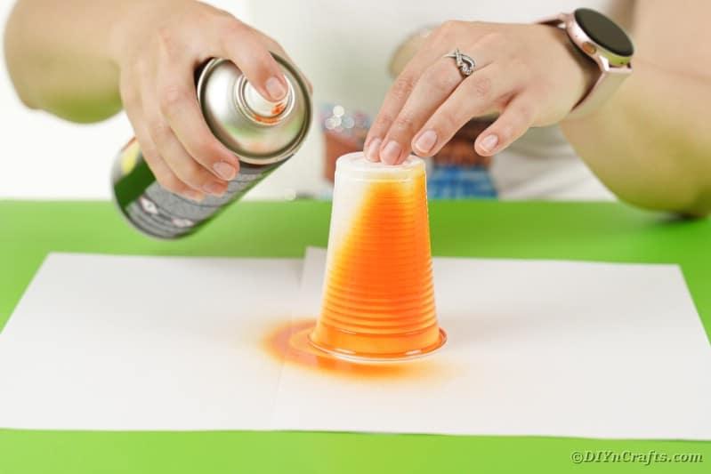 Spraying a cup orange