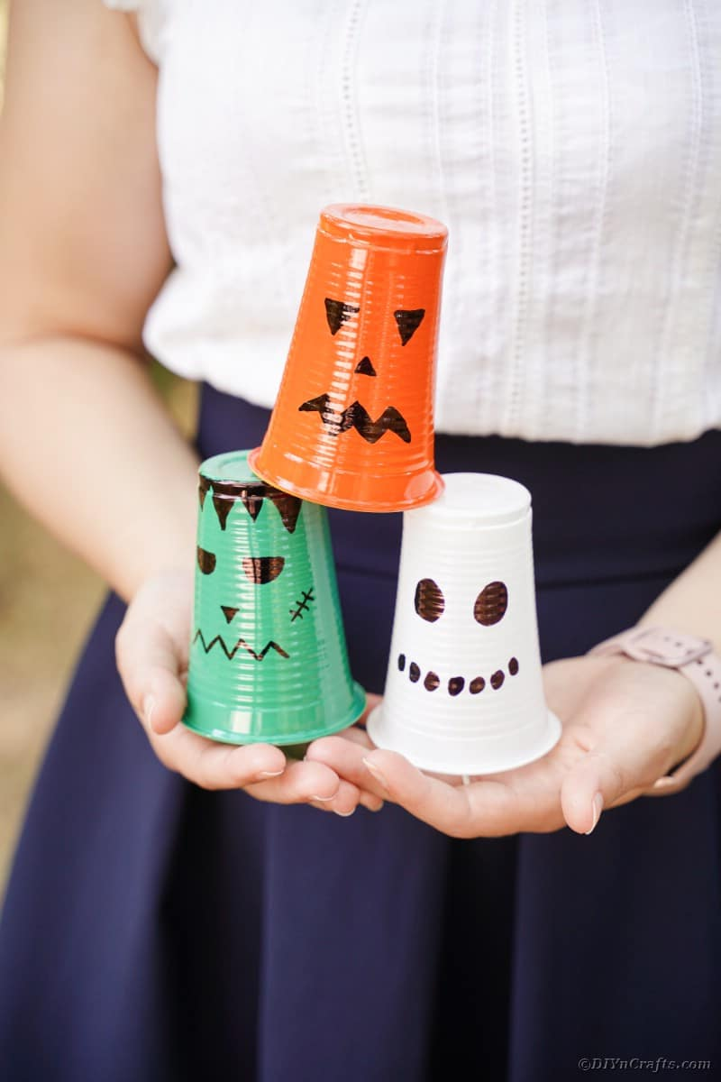 Woman holding plastic cup lanterns