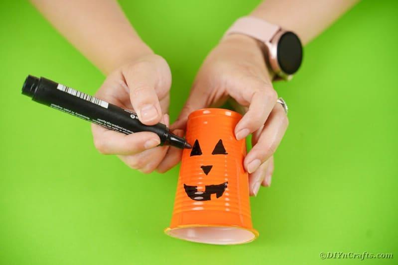 Drawing face on pumpkin lantern