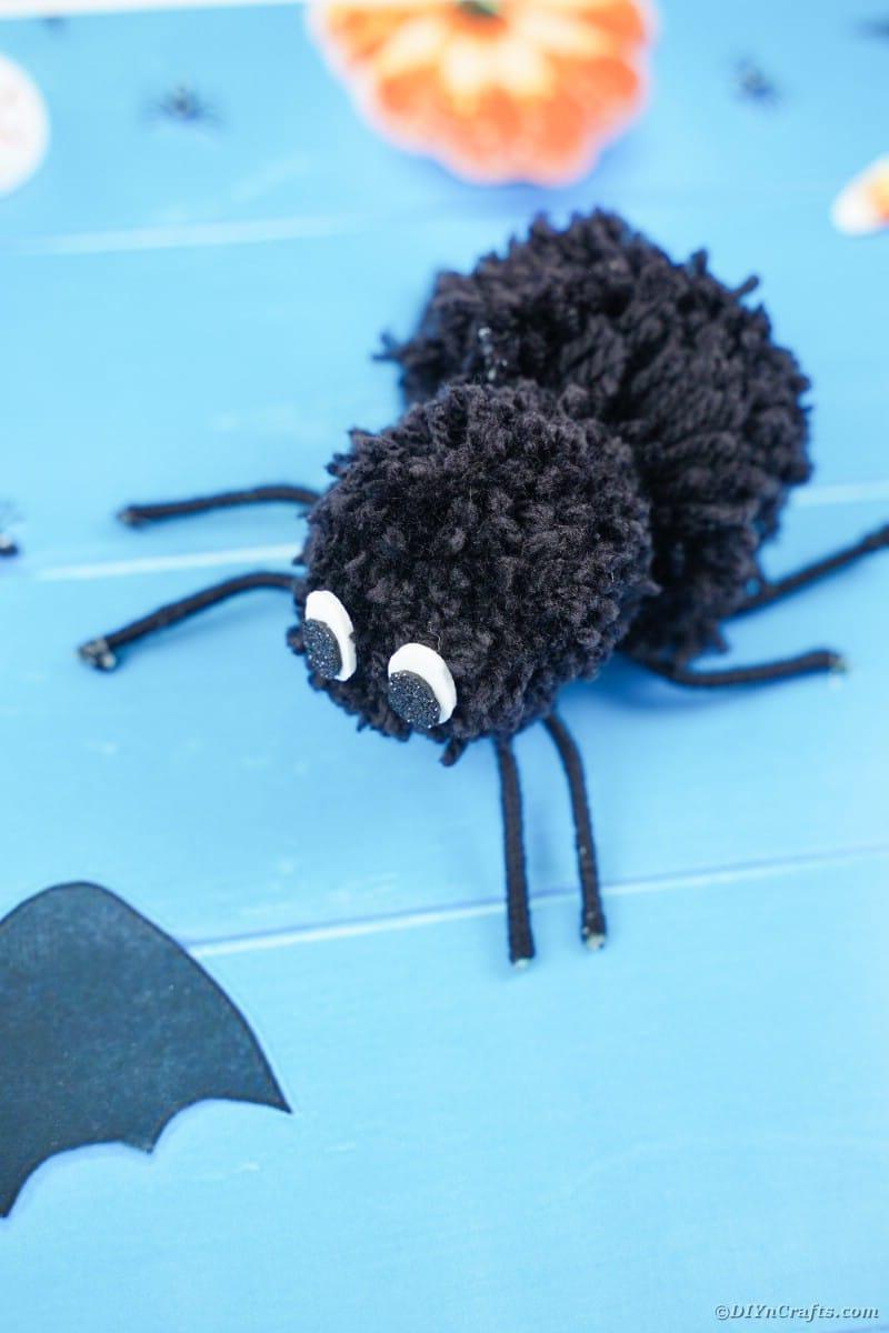 Pom pom spider on blue halloween paper