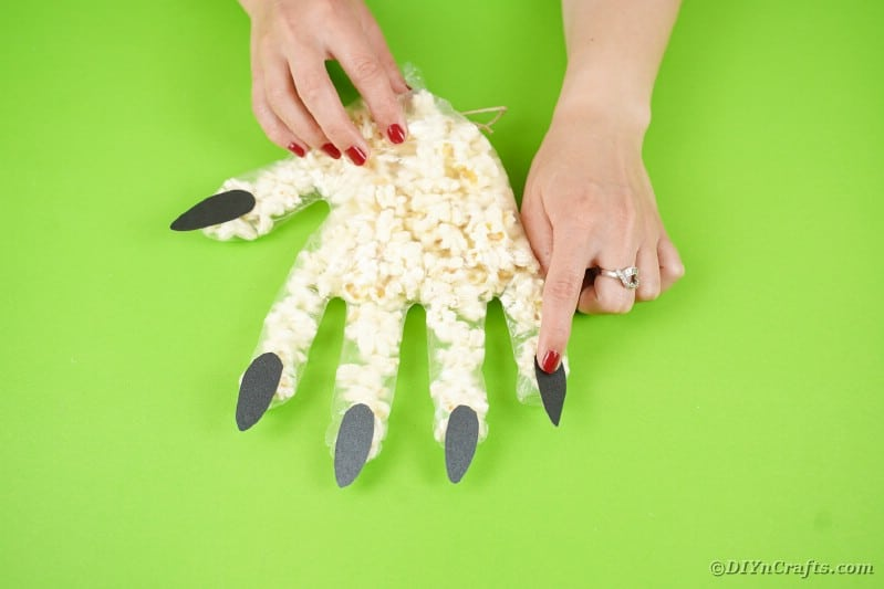 Gluing nails on fingers of glove