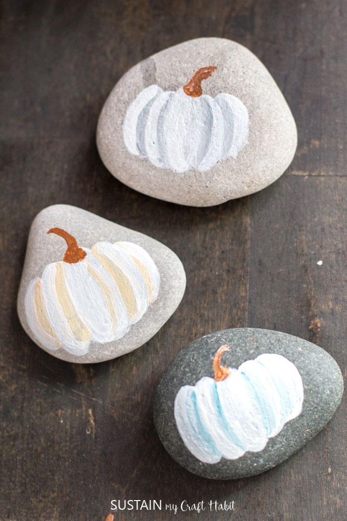 Rocks painted with white pumpkins