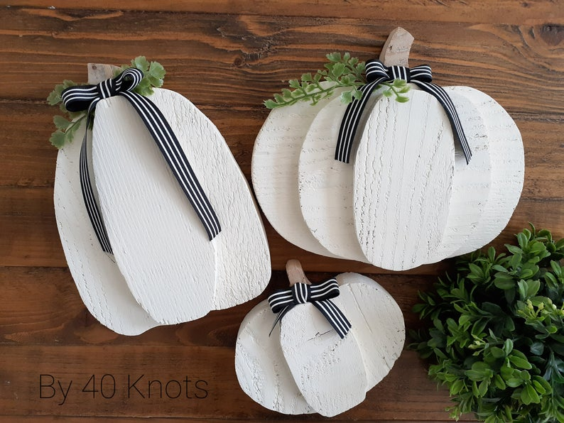 White wooden pumpkins on wood surface
