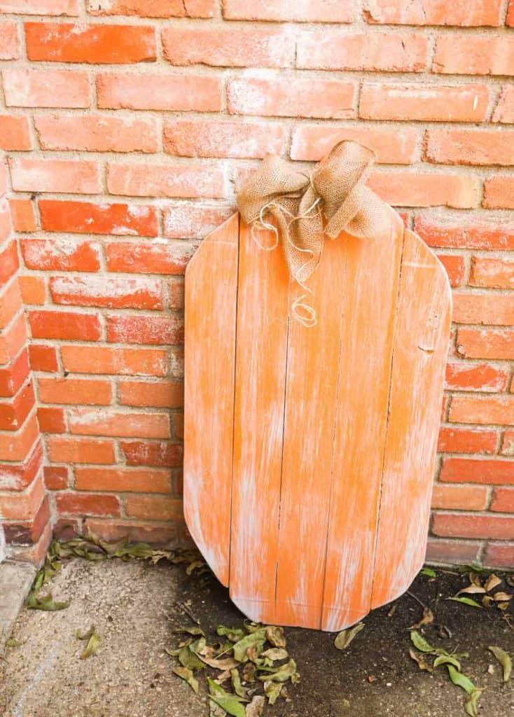 Wood pumpkin against brick wall