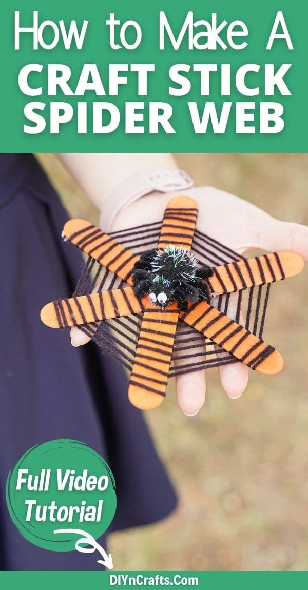 Woman holding craft stick spider web