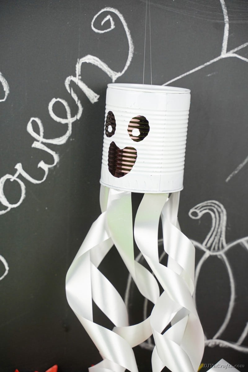 Tin can ghost by chalkboard wall
