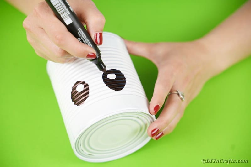 Drawing eyes onto tin can