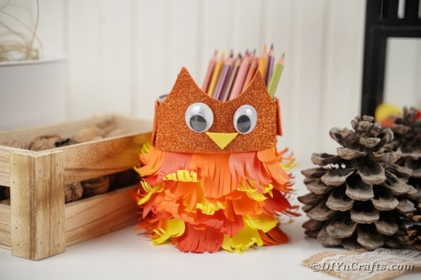 Tin can owl by wooden box