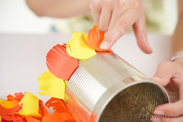 Gluing feathers onto tin can