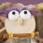 Wooden owl with purple feathers on table