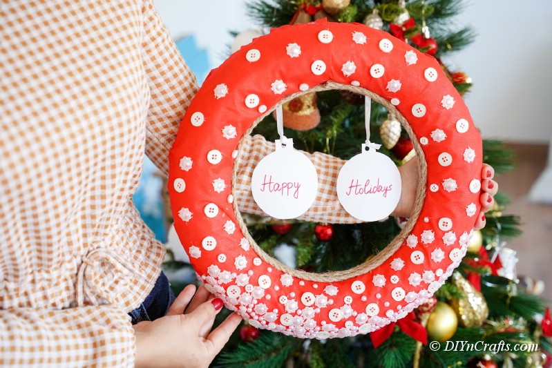 woman holding red christmas wreath