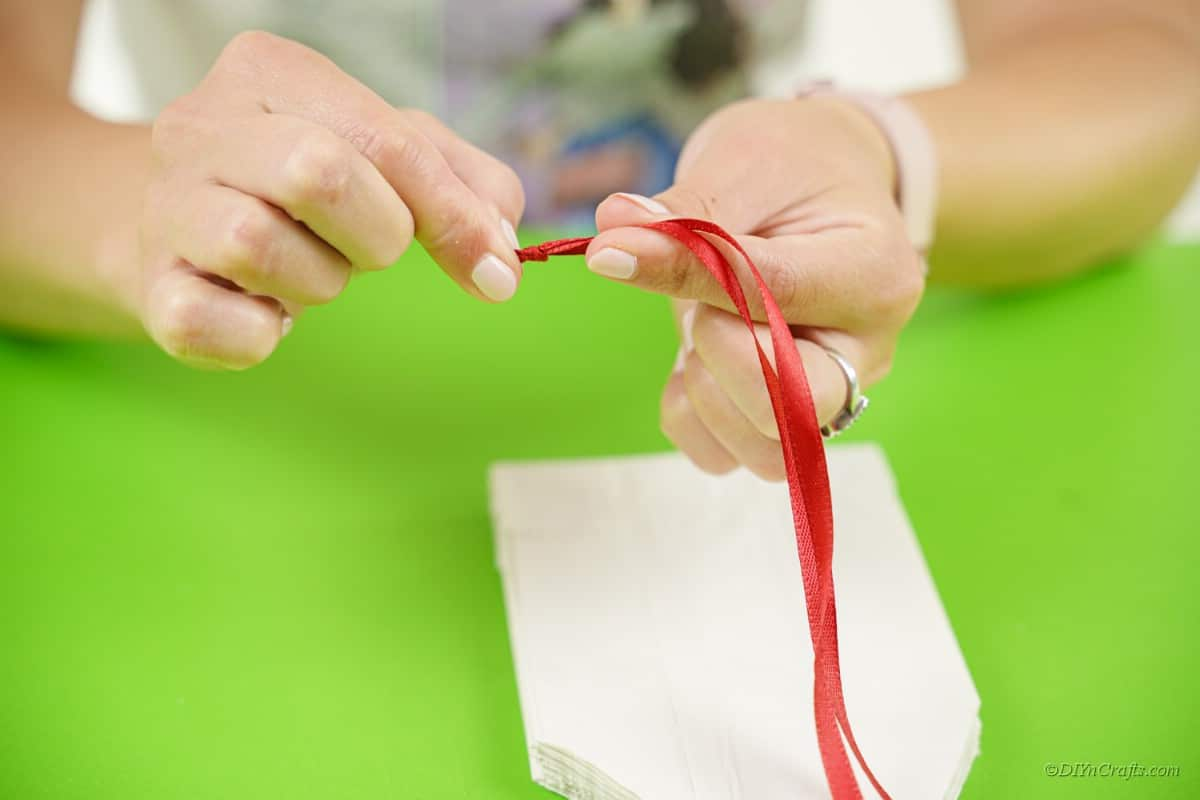 woman pinching red ribbon for craft project