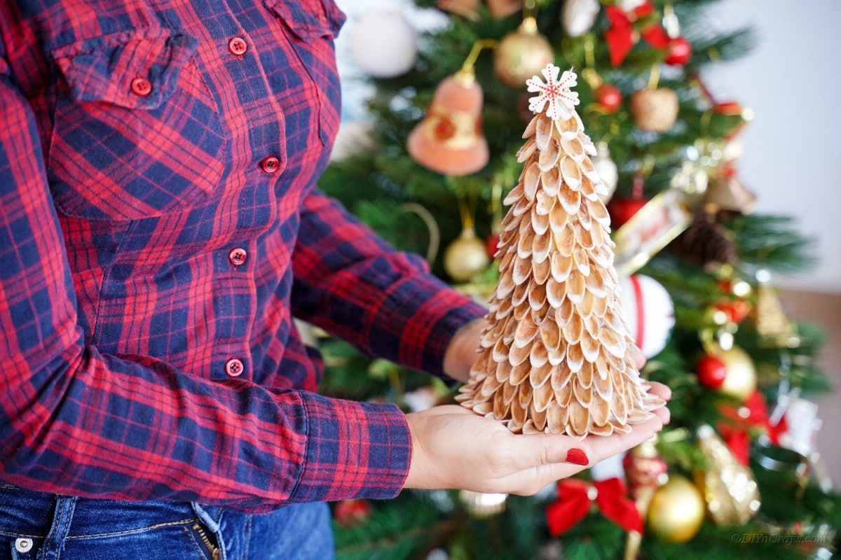 Person holding pistachio shell Christmas tree craft decoration