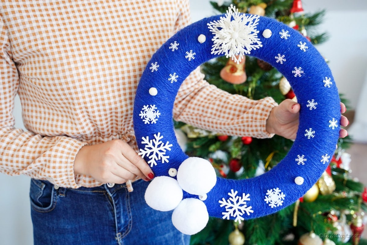 woman holding blue and white winter themed wreath