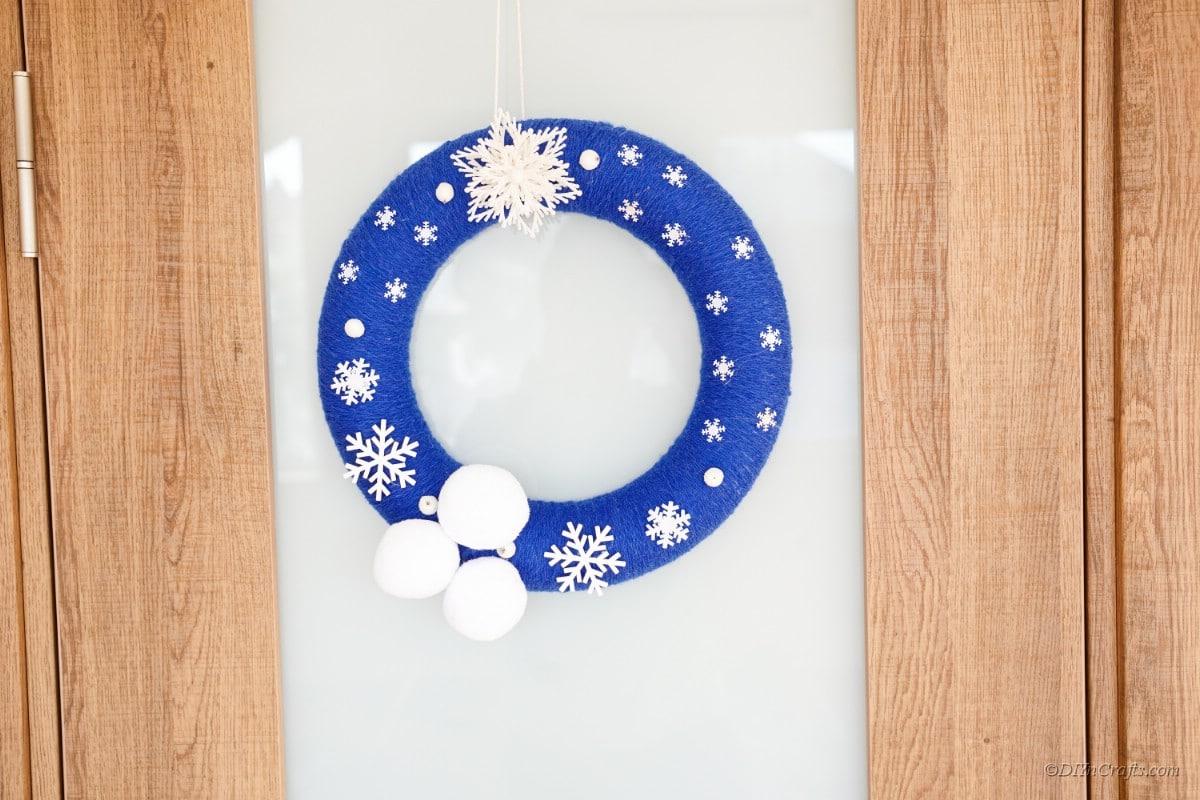 Schneeflockenkranz hing an Glas- und Holztür