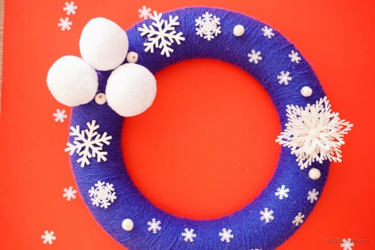 white and blue wreath with foam poms and snowflakes